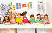 pic of kindergarten  - Big group of diverse looking preschool boys and girls play with modeling clay in class in kindergarten - JPG
