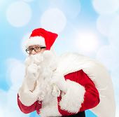 christmas, holidays and people concept - man in costume of santa claus with bag making hush gesture over blue lights background