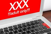 Online Porn Concept. Xxx Adults Only Message On Silver Laptop And Red Xxx Button On Keyboard.