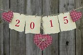 Year 2015 on antique parchment paper hanging on clothesline with red hearts and wooden background