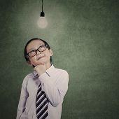 Little Businessman Under Lit Bulb With Copyspace