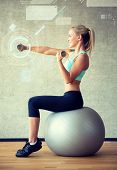 fitness, sport, training, future technology and lifestyle concept - smiling woman with dumbbells and exercise ball in gym and projection