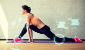 fitness, sport, training, future technology and lifestyle concept - smiling woman stretching leg on mat in gym and projections