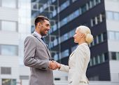 business, partnership, gesture success and people concept - smiling businessman and businesswoman shaking hands over office building