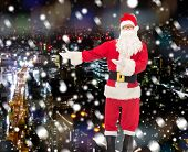 christmas, holidays, gesture and people concept - man in costume of santa claus over snowy night cit poster