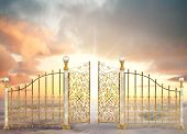 image of gate  - Pearly gates of heaven opening to a high altitude sunrise between two layers of clouds in a landscape orientation - JPG