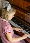 the young girl learns to play a piano