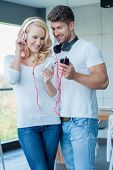 Happy Young White Couple in Casual Outfits  Listening Music from Mobile Phone Using Headphones.