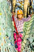 Little girl climbing in adventure park