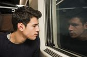 Young Man Travelling In Train Looking Out Of Window
