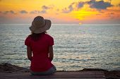image of rear-end  - Young woman in hat sitting on the coast and looking at sunset - JPG