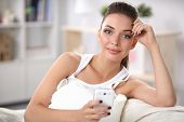 Cheerful pretty woman in her living room sitting on the couch sending messages