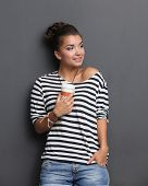 Portrait of a young woman with cup of tea or coffee, isolated.