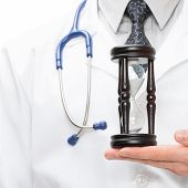 Doctor Holdling In His Hand A Hourglass
