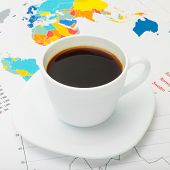Coffee Cup Above World Map And Some Financial Documents