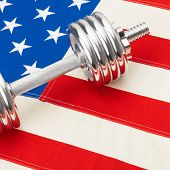 Metal Dumbbells Over Usa Flag As Symbol Of Healthy Nation - Studio Shot
