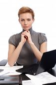 Portrait of attractive young businesswoman with short hair, sitting at desk, thinking.