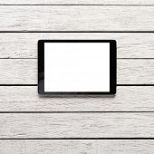 Digital tablet computer with isolated screen on white wooden desk.