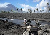 image of luzon  - man working to clear river with water buffalo off debris from eruption of mount mayon in albay province luzon island in the philippines - JPG