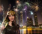 Young brunette woman with champagne glass in city at night. Celebration theme.