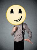Businessman holding a yellow smiley face emoticon in front of his head