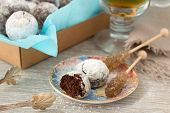 foto of sugar  - Chocolate homemade cookies in powdered sugar with tea and caramel sugar on a wooden background - JPG