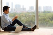 picture of concentration man  - Asian man sitting at the window and text messaging - JPG
