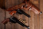 picture of revolver  - Three revolvers with bullets on a wooden background - JPG
