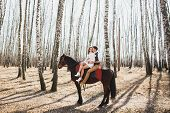 foto of brown horse  - romantic walk of bride and groom man and a woman riding together brown horse - JPG