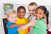 stock photo of preschool  - a group of little preschool friends hugging in a circle in classroom - JPG