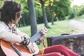stock photo of hippy  - Hippie woman playing guitar - JPG