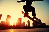 picture of skateboarding  - young skateboarder skateboarding ollie trick at sunrise city - JPG