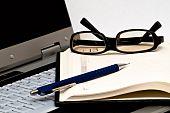 Glasses, pen and open agenda on laptop