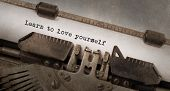 stock photo of old vintage typewriter  - Vintage typewriter old rusty and used learn to love yourself - JPG