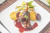 stock photo of lamb shanks  - A plate full of lamb shank red wine sauce polenta beetroot and salad - JPG