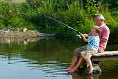 stock photo of grandfather  - Photo of grandfather and grandson sitting on pontoon with their feet in water and fishing on weekend - JPG