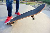 stock photo of skateboarding  - young skateboarder legs skateboarding at skatepark ramp