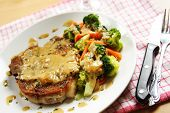picture of pork chop  - a pan fried pork chop with coconut sauce and vegetables on the side - JPG