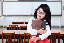 picture of indian apple  - Female elementary school student back to school and standing in the class while holding a book and apple - JPG