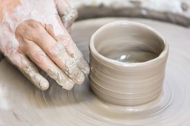 pic of pottery  - A woman is making a pottery cup on the pottery wheel - JPG