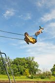 foto of young girls  - Young girl on swing against a blue sky - JPG