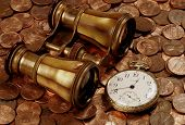 image of financial management  - opera glasses and a pocketwatch atop coins portrays financial navigation and business direction - JPG