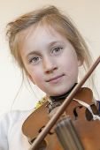 Close Up Of A Child Playing Violin On Isolated Light Background. Portrait Of Girl With String And Pl poster