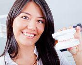 Mulher segurando uma amostra de dentes ou próteses no dentista