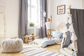 Boy Playing With A Toy In A Cozy Child Playroom Interior poster