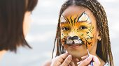 Kids Facial Art. Little Girl Getting Her Face Painted By Face Painting Artist Like Tiger, Free Space poster