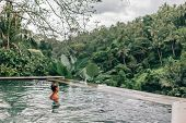 Human relaxing in Bali infinity pool with jungle view  poster