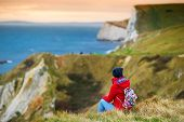 Tourist Enjoying View Of Man Owar Cove On The Dorset Coast In Southern England, Between The Headlan poster