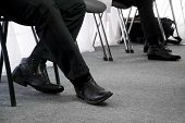 The Legs Of The Unemployed, Waiting For Their Turn For An Interview, Sitting On Office Chairs In The poster