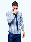 Handsome business man wearing tie tired rubbing nose and eyes feeling fatigue and headache. Stress a poster